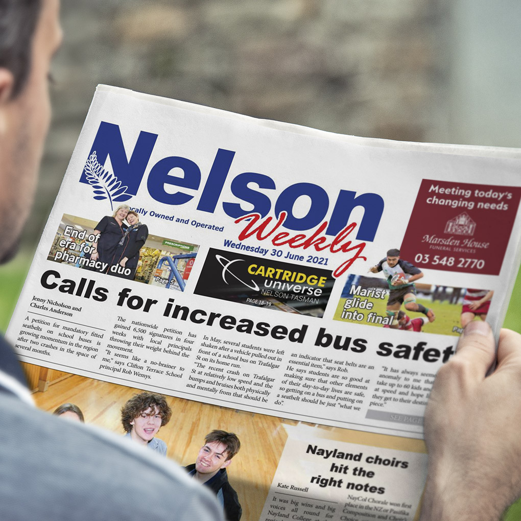 A person reading the Nelson Weekly